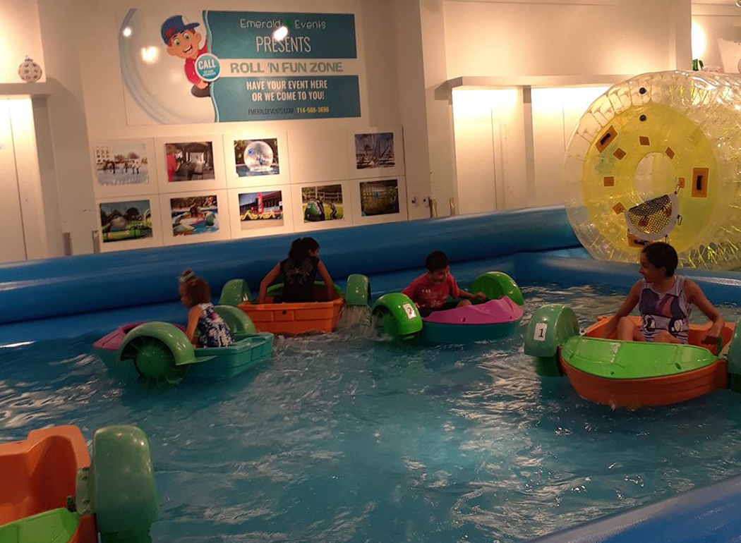 A Group Of Children Paddling Around In Tiny Paddle Boats