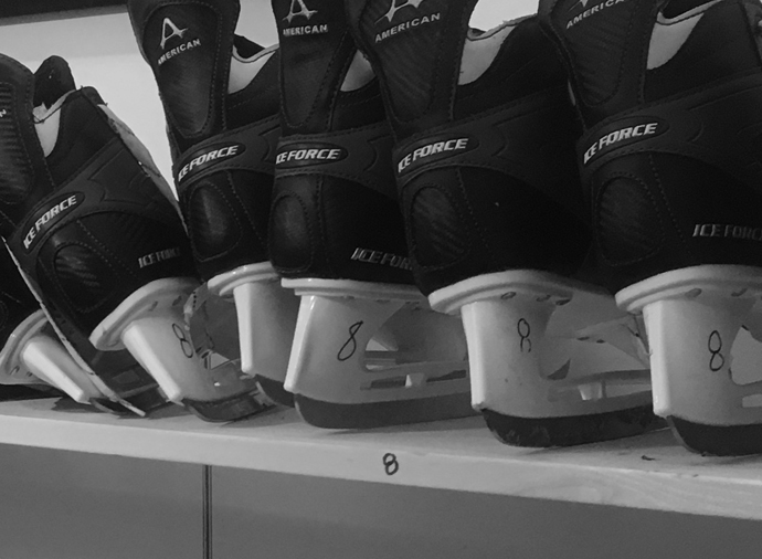 Image os black ice skates with gray trim. Used for indoor ice skating. $1 skate rentals