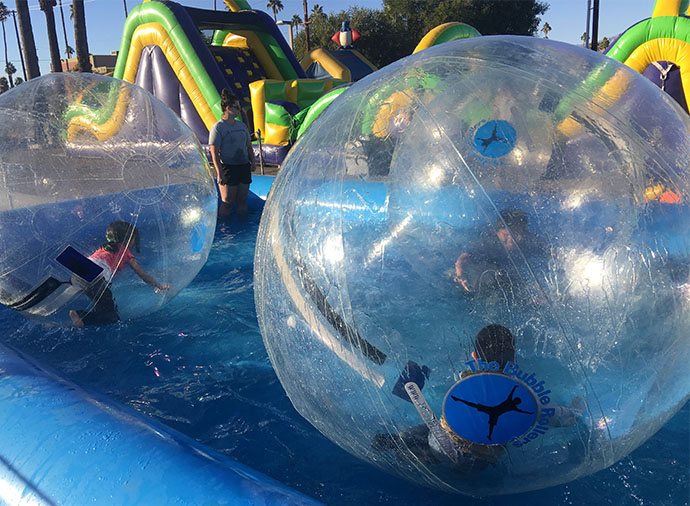 Image of kids rolling around in plastic bubbles in an inflateble pool during an outdoor event