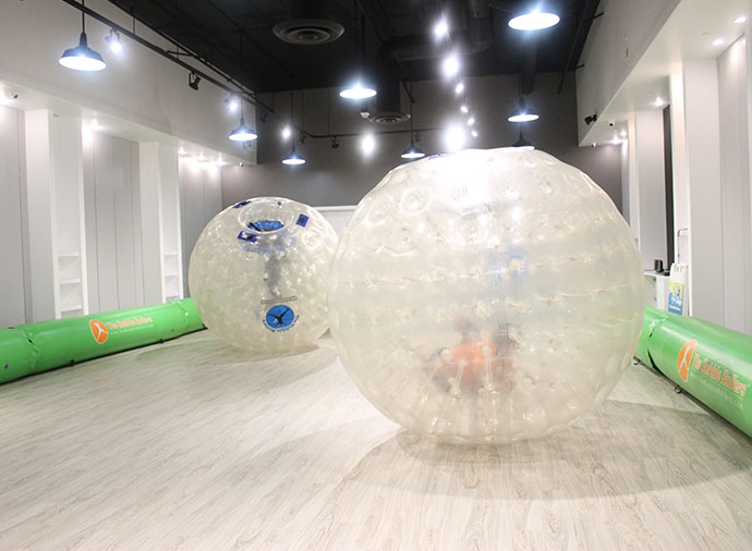 Image of kids rolling around in Large Plastic balls indoors