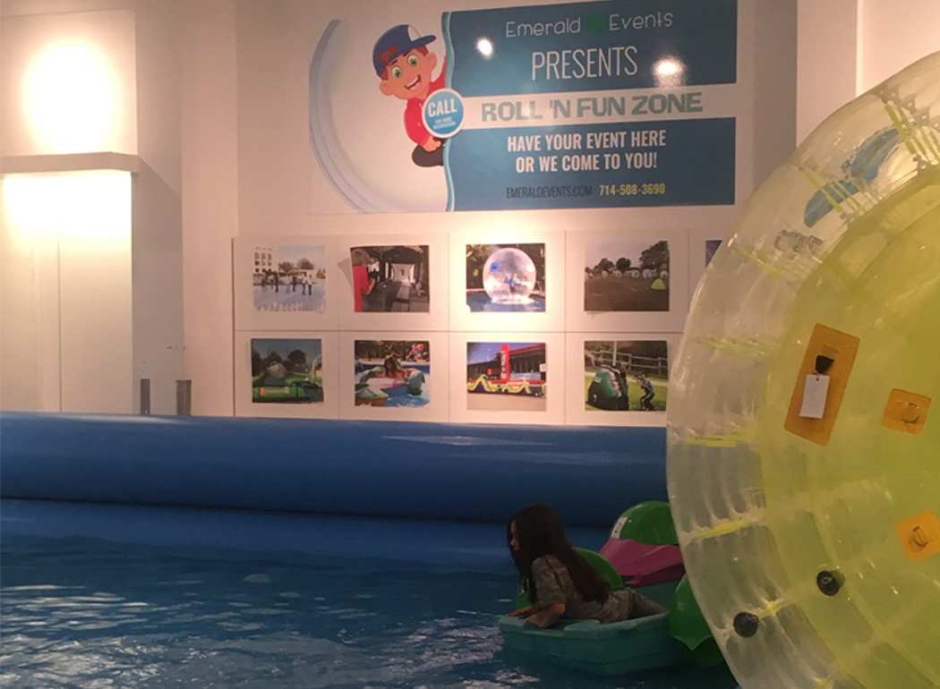 Girl riding on a paddle roller on an inflatable pool at Roll N Fun Zone in South Bay Galleria Mall