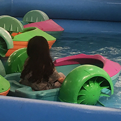 Little girl riding in a paddle roller at Roll and Fun Zone